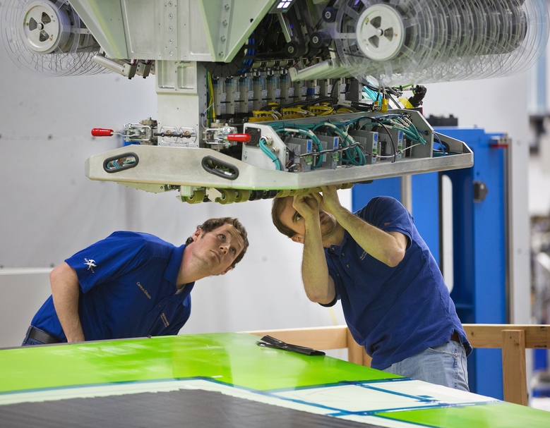 Engineers Cameron Gillespie, left and Andy Stulc examine the head of an Automatic Fiber Placement machine made by ElectroImpact. The Mukilteo company designs these AFP machines that lay down composite tape in different shapes and configurations to make wing spars and skins for the new Boeing 777 wings.